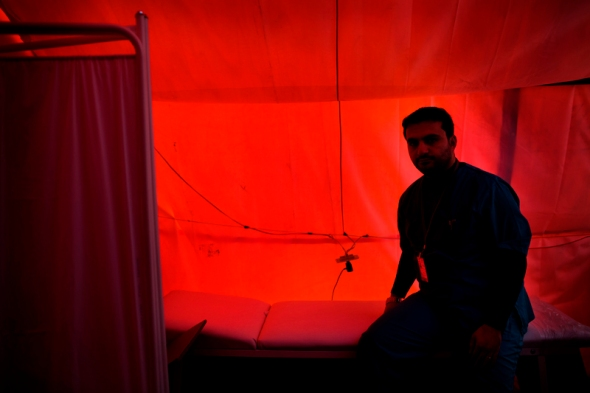 A Syrian doctor sits in the improvised medical clinic in the refugee camp waiting for patients. He was contacted by the rebels and asked if he would come to the camp to assist the many refugees. Before the war he worked with plastic surgery. The trip to the camp would normally take a little less than a day. This time he spend four days on the road getting here due to the fear of the government army.