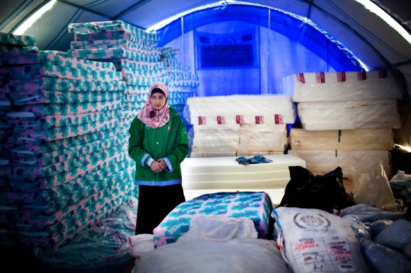 A NGO worker stands in one of two tents acting as storage for the supplies that comes in through Turkey.